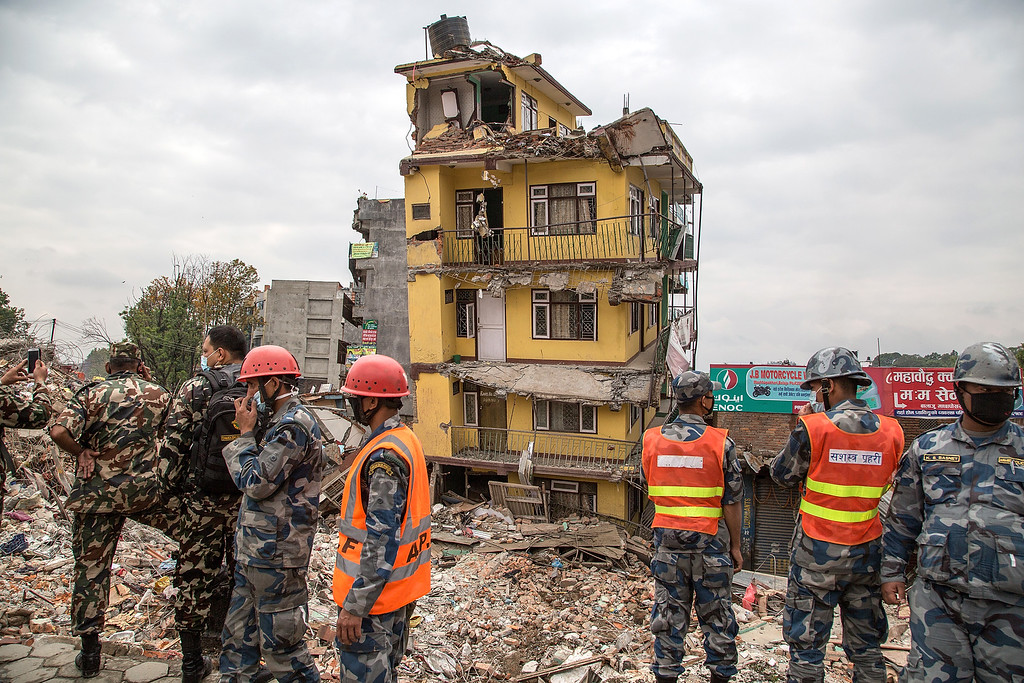 . Members of the Nepali army stand in front of a collapsed building near Gangabu on April 30, 2015 in Kathmandu, Nepal. A major 7.8 earthquake hit Kathmandu mid-day on Saturday, and was followed by multiple aftershocks that triggered avalanches on Mt. Everest that buried mountain climbers in their base camps. Many houses, buildings and temples in the capital were destroyed during the earthquake, leaving over 5500 dead and many more trapped under the debris as emergency rescue workers attempt to clear debris and find survivors. Regular aftershocks have hampered recovery missions as locals, officials and aid workers attempt to recover bodies from the rubble.  (Photo by Omar Havana/Getty Images)