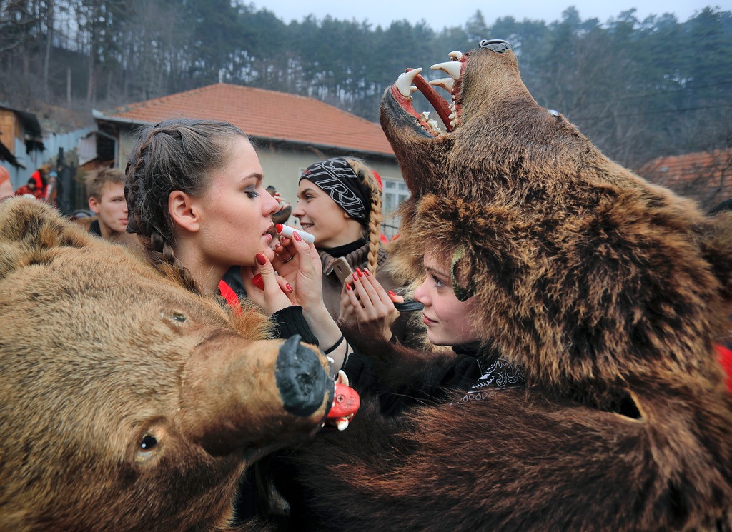. In this Saturday, Dec. 30, 2017 picture Raluca Atrejei, right, helps Roxana Stan, apply lipstick as they get ready for an annual bear parade in Comanesti, Romania. The tradition, originating in pre-Christian times, when dancers, wearing colored costumes or animal furs, went from house to house in villages singing and dancing to ward off evil, has moved to Romania\'s cities, where the ritual is performed for money.(AP Photo/Vadim Ghirda)