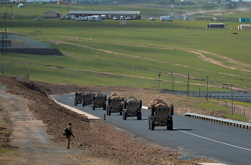 . A man looks on as a military convoy passes by before the funeral procession of former South African President Nelson Mandela in Qunu on December 15, 2013. Mandela, the revered icon of the anti-apartheid struggle in South Africa and one of the towering political figures of the 20th century, died in Johannesburg on December 5 at age 95.       AFP PHOTO / FILIPPO MONTEFORTEFILIPPO MONTEFORTE/AFP/Getty Images