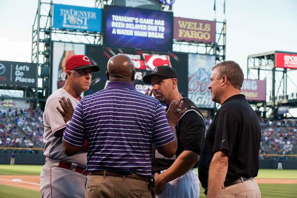 . DENVER, CO - AUGUST 16:  Colorado Rockies manager Walt Weiss #22 and Cincinnati Reds manager Bryan Price #38 discuss a situation with a broken water main with Director of Major League Operations Paul Egins and the postponement of the game at Coors Field on August 16, 2014 in Denver, Colorado. The game between the Cincinnati Reds and the Colorado Rockies was postponed to August 17. (Photo by Dustin Bradford/Getty Images)