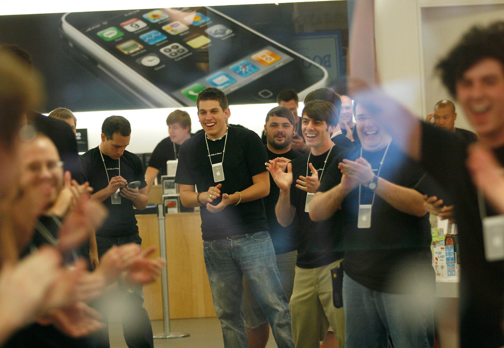 . Southpark Mall Apple store employees cheer as the first customers to buy the new iPhone enter the store Friday evening, June 29, 2007, in Charlotte, N.C. More than 140 people lined up to purchase Apple\'s latest product. (AP Photo/Jason E. Miczek).