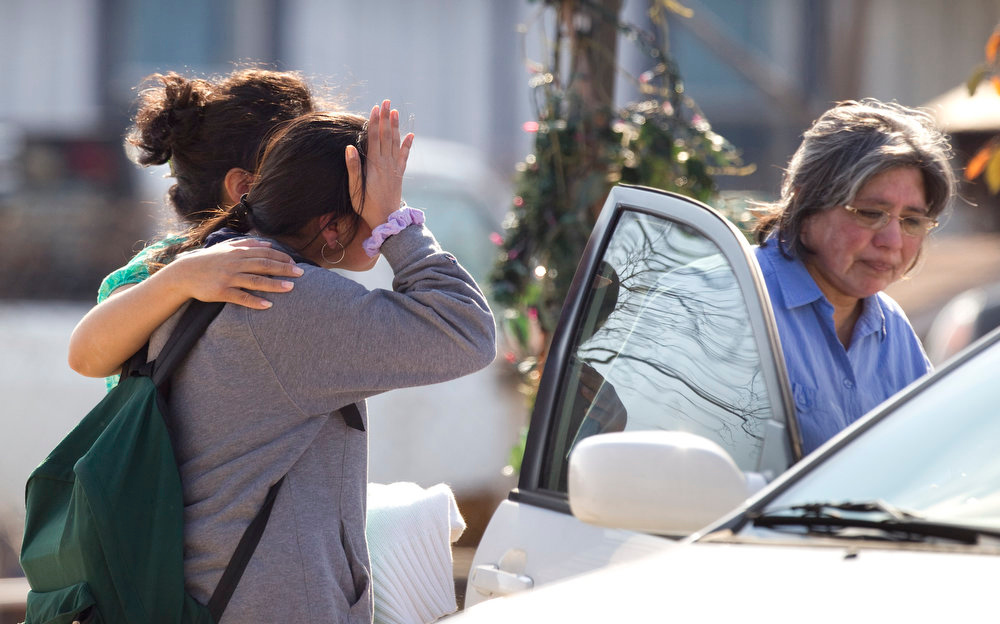 . Ana Leal, left, embraces Lone Star College student Sabrina Cuellar after she was evacuated and picked up by her mother, Maria Cuellar, right, from the campus following a shooting at the north Harris County school Tuesday, Jan. 22, 2013, in Houston.   Authorities say the shooting was the result of an altercation between two people, and at least one was a student.   (AP Photo/Houston Chronicle, Brett Coomer)
