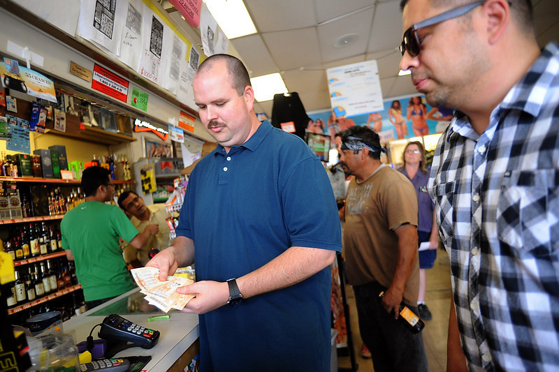 """. Norman Seeman buys 00 worth of Powerball tickets at Alcon Liquor in Canoga Park, CA Friday.  The liquor store is listed as a \""""Lucky Retailer\"""" on the California Lottery website.  By Friday at noon the Powerball jackpot had grown to an estimated 00 million, the largest amount in the game\'s history.(Andy Holzman/Staff Photographer)"""