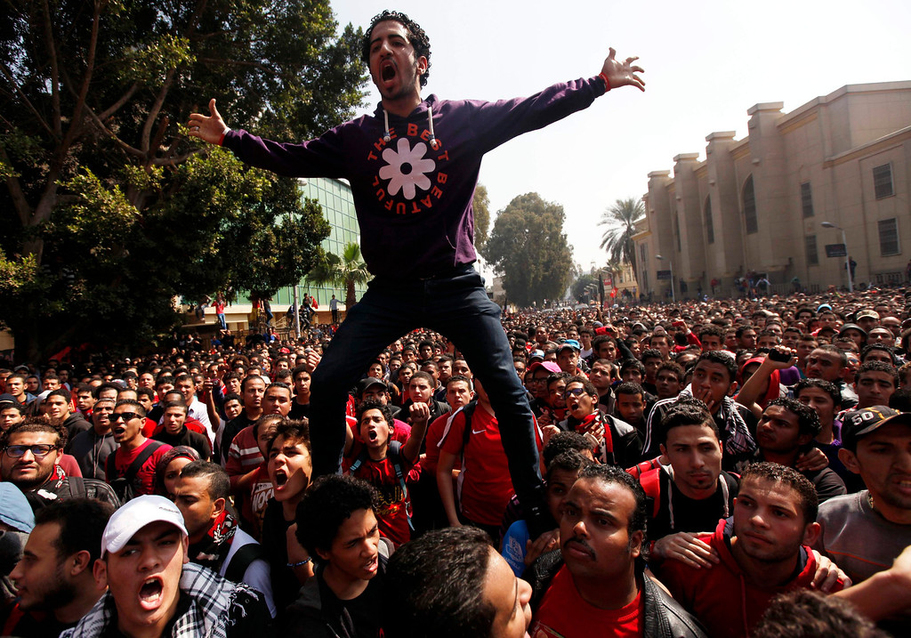 """. Al-Ahly fans, also known as \""""Ultras\"""", celebrate and shout slogans in front of the Al Ahly club after hearing the final verdict of the 2012 Port Said massacre in Cairo March 9, 2013. REUTERS/Amr Abdallah Dalsh"""