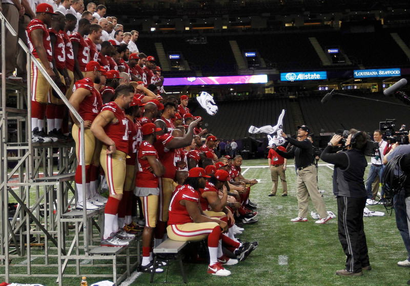 . San Francisco 49ers head coach Jim Harbaugh collects towels from his players as they pose for a team picture during Media Day for the NFL\'s Super Bowl XLVII in New Orleans, Louisiana January 29, 2013. The 49ers will meet the Baltimore Ravens in the game on February 3. REUTERS/Joe Skipper