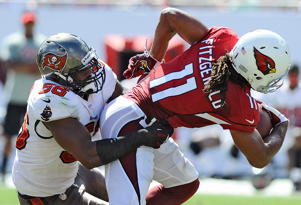 . Tampa Bay Buccaneers linebacker Dekoda Watson (56) stops Arizona Cardinals wide receiver Larry Fitzgerald (11) after a reception during the third quarter of an NFL football game on Sunday, Sept. 29, 2013, in Tampa, Fla. (AP Photo/Brian Blanco)
