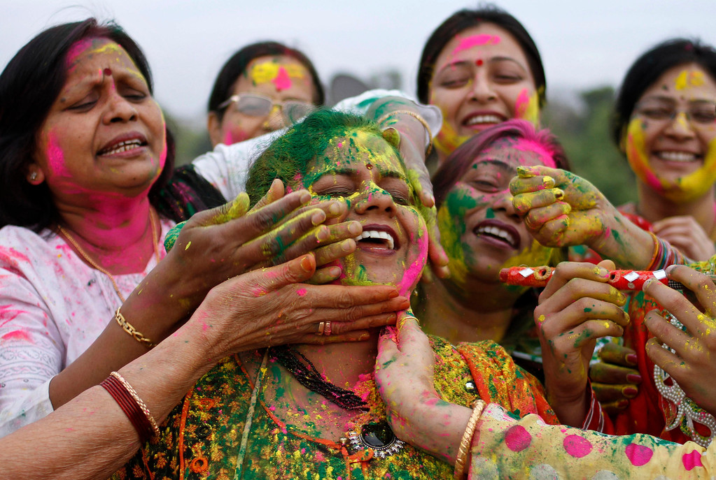 ". Indian women smear colors on each others faces as they celebrate ""Holi\"", the Indian festival of colors in Allahabad, India, Tuesday, March 26, 2013. Holi, the Hindu festival of color heralds the arrival of spring.(AP Photo/ Rajesh Kumar Singh)"