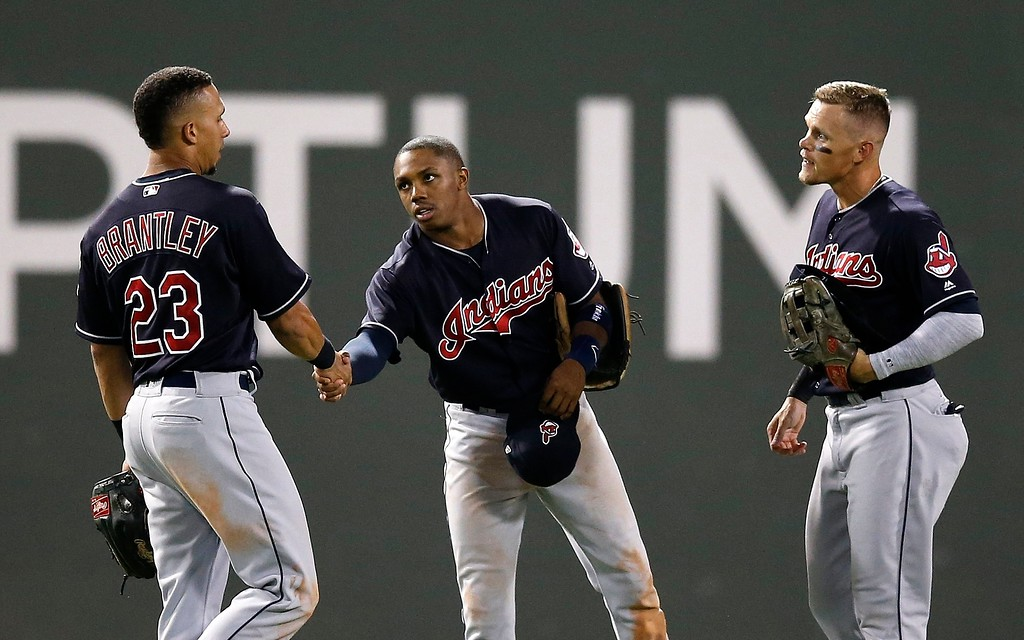 . Cleveland Indians\' Michael Brantley (23), Greg Allen, center, and Brandon Guyer celebrates after defeating the Boston Red Sox during a baseball game in Boston, Tuesday, Aug. 21, 2018. (AP Photo/Michael Dwyer)