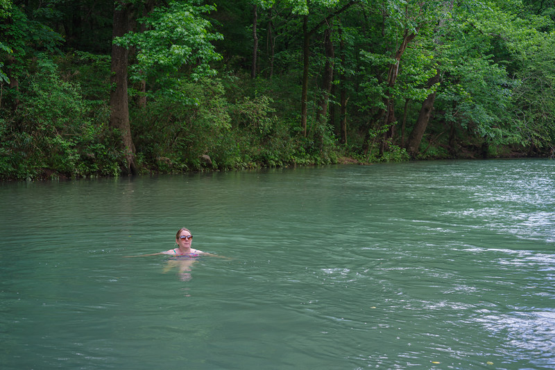 A swimmer wearing sunglasses swims in a swimming hole in the jungle