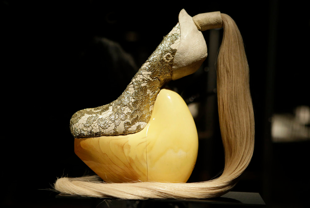 Description of . A shoe, designed by Masaya Kushino, and made with lacquered Japanese cypress wood, human hair, and lace, displayed at the