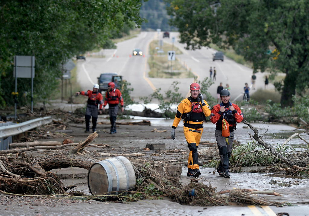 . Summit County Rescue\'s Zak Slutzky, left, and Colin Dinsmore walk across a debris filled bridge near Lefthand Canyon Road after rescuing four separate people from flooded homes, Friday, Sept. 13, 2013 in Boulder, Colo. By truck and helicopter, thousands of people stranded by floodwaters came down from the Colorado Rockies on Friday, two days after seemingly endless rain turned normally scenic rivers and creeks into coffee-colored rapids that wrecked scores of roads and wiped out neighborhoods. (AP Photo/The Daily Camera, Jeremy Papasso) NO SALES