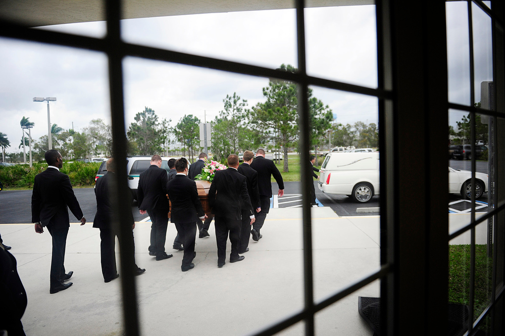 Description of . Pallbearers carry the casket of Mindy McCready during her funeral ceremony at the Crossroads Baptist Church in Fort Myers, Fla., on Tuesday, Feb. 26, 2013.  McCready committed suicide Feb. 17 at her home in Arkansas, days after leaving a court-ordered substance abuse program. (AP Photo/Naples Daily News, Corey Perrine)