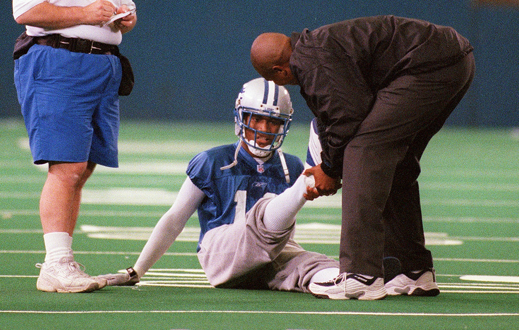 . Detroit Lions wide receiver and draft pick Scotty Anderson (bottom, #18) is tended to by team personnel after hurting his foot while being tackled during minicamp, held inside the Silverdome in Pontiac, Mich., Friday, June 1, 2001.