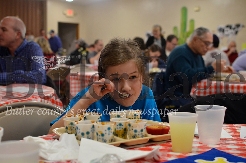 Elise Bachman, 9, samples the nine chilis competing in the thirteenth annual chili cook-off at Saint Andrews United Presbyterian Church. The event is co-hosted by the church and Butler's Operation Spay and Neuter organization. Tanner Cole/Butler Eagle