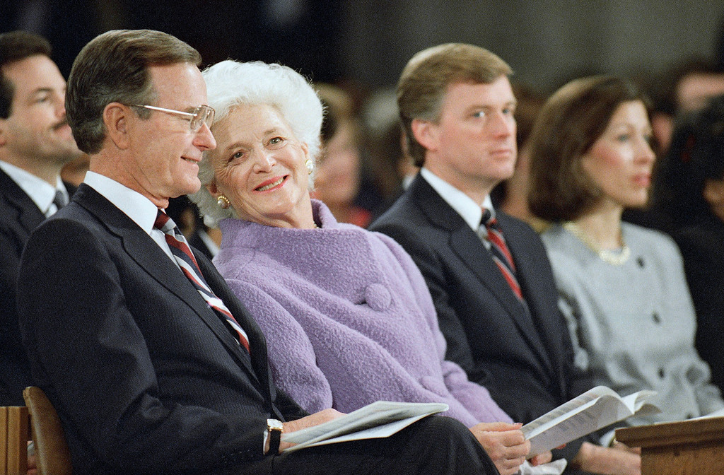 . First Lady Barbara Bush, second from left, leans over to talk with her husband, President George H. W. Bush, left, during the National Prayer Service at the Washington Cathedral, Sunday, Jan. 22, 1989, Washington, D.C. At right is Vice President Dan Quayle and his wife, Marilyn Quayle. (AP Photo/Doug Mills)