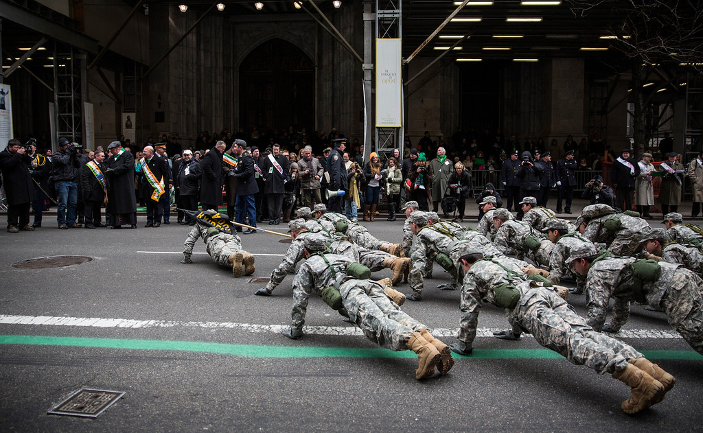 . Members of the military do push-ups in front of St. Patrick\'s Cathedral while marching in the annual St. Patrick\'s Day Parade along Fifth Ave in Manhattan on March 17, 2014 in New York City. Political controversy surrounded this year\'s parade, as New York City Mayor Bill De Blasio decided not to march due to the parade organizer\'s policy to ban participants that identify themselves as lesbian, gay, bisexual or transgender.  Heineken and Guinness announced earlier that they would drop their sponsorship of the parade for along the same reasons. (Photo by Andrew Burton/Getty Images)