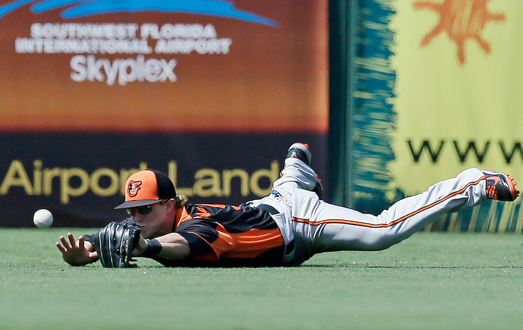 . Baltimore Orioles left fielder Nate McLouth dives but can\'t handle a double by Minnesota Twins\' Chris Parmelee in the fifth inning of an exhibition spring training baseball game in Fort Myers, Fla., Tuesday, March 26, 2013. (AP Photo/Elise Amendola)