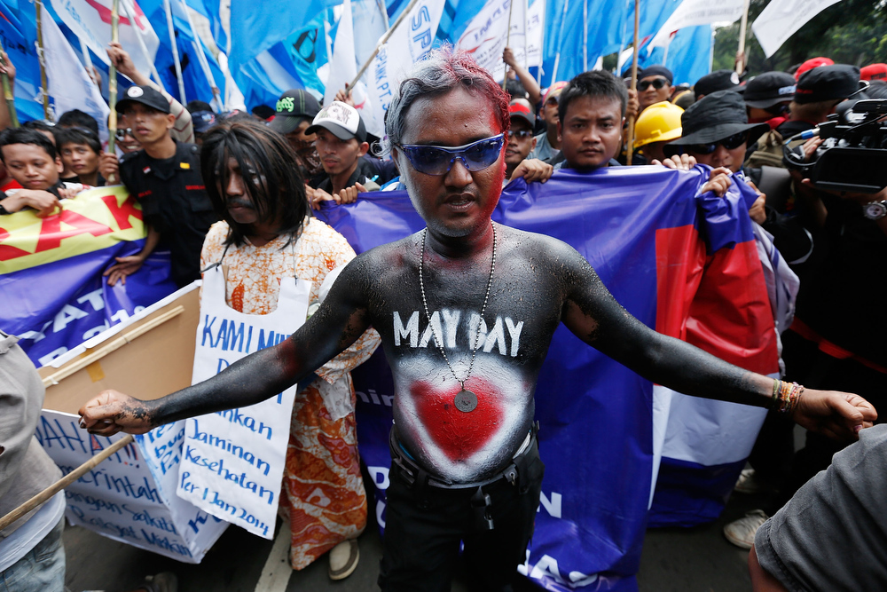 Description of . A May Day demonstrator in bodypaint leads a group of union members and activists in a demonstartion in front of the Presidential Palace May 1, 2013 in Jakarta, Indonesia.  Tens of thousands of workers and labor activists marched through Jakarta's central business district, demanding the implementation of higher minimum wages and better working conditions.  (Photo by Ed Wray/Getty Images)