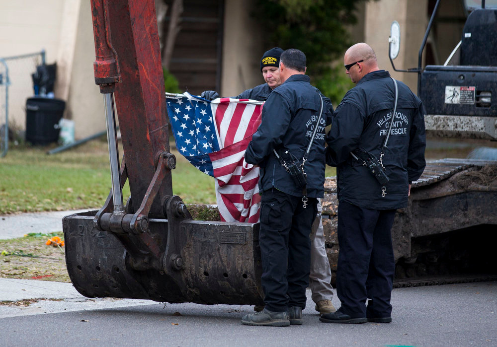 . Hillsborough County firefighters recover a U.S. flag from the house, where Jeffrey Bush was swallowed by a sinkhole, before its demolition in Seffner, Florida March 3, 2013. Florida rescue workers ended their efforts on Saturday to recover the body of Jeffrey Bush, who disappeared into the sinkhole that swallowed his bedroom while he slept and demolished the suburban Tampa home due to its dangerous conditions, a rescue spokeswoman said.  REUTERS/Scott Audette