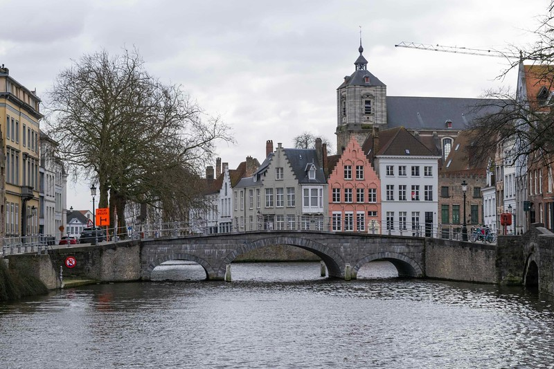 low rising bridge over river with traditional houses in the background