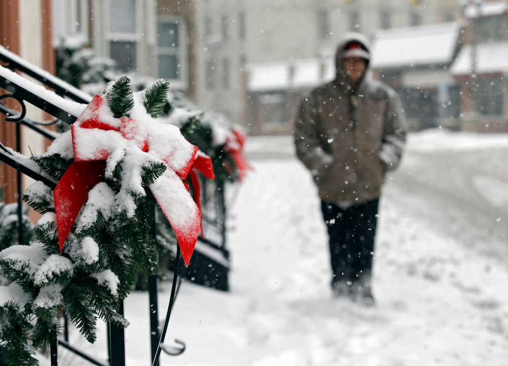 Description of . A man walks past snow-covered Christmas decorations on apartments in Berea, Ohio Wednesday, Dec. 26, 2012. The National Weather Service posted blizzard warnings for a swath of Ohio from the Indiana border stretching northeast to the Lake Erie region. (AP Photo/Mark Duncan)1
