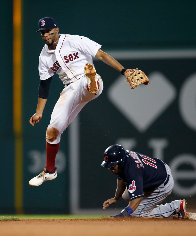 . Cleveland Indians\' Jose Ramirez (11) is forced out at second base as Boston Red Sox\'s Xander Bogaerts turns the double play on Yandy Diaz during the ninth inning of a baseball game in Boston, Tuesday, Aug. 21, 2018. (AP Photo/Michael Dwyer)