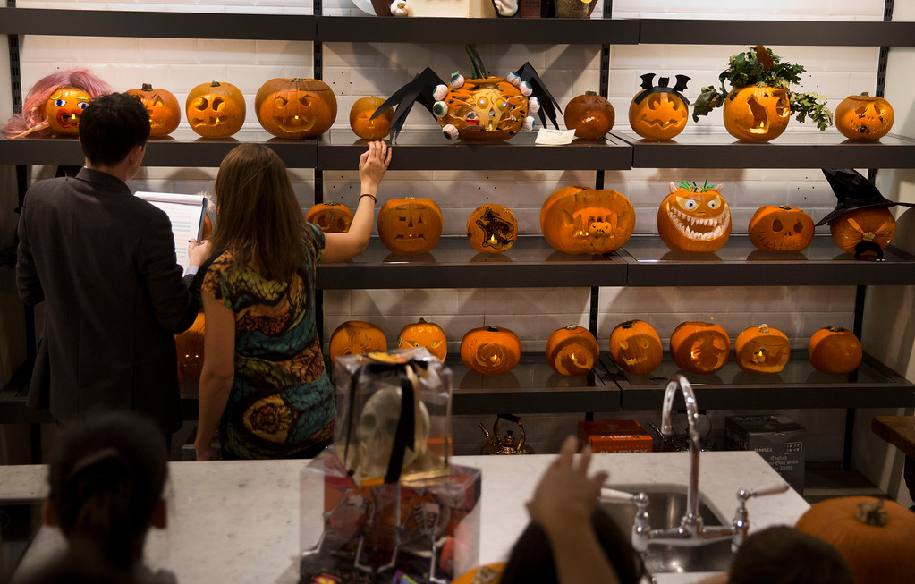 . Designs are judged during a children\'s pumpkin carving competition at the Fortnum & Mason department store in London, Thursday, Oct. 31, 2013. Pumpkins are traditionally carved with decorative faces by people to mark Halloween which occurs annually around the world on October 31. (AP Photo/Matt Dunham)