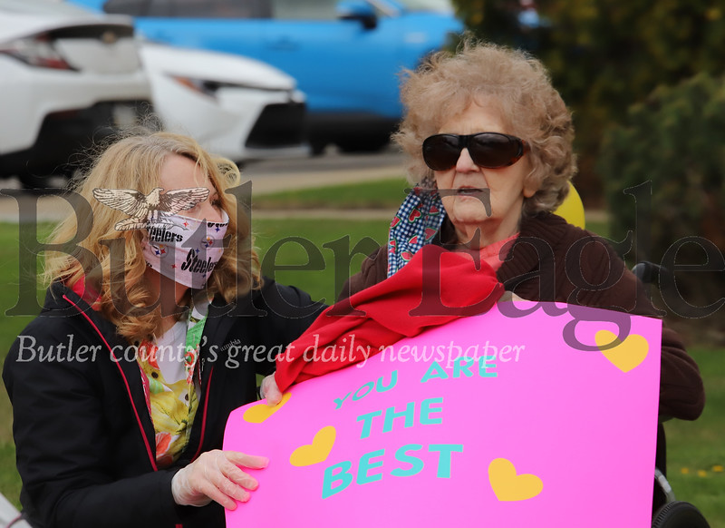 Concordia Lund Care Center resident Babe Hugo holds up a sign to her family in Friday's Wave Parade at the facility in Cabot. Family's of resident's were able to drive by the building's entrance to greet relatives on lockdown during the COVID-19 crisis. Seb Foltz/Butler Eagle