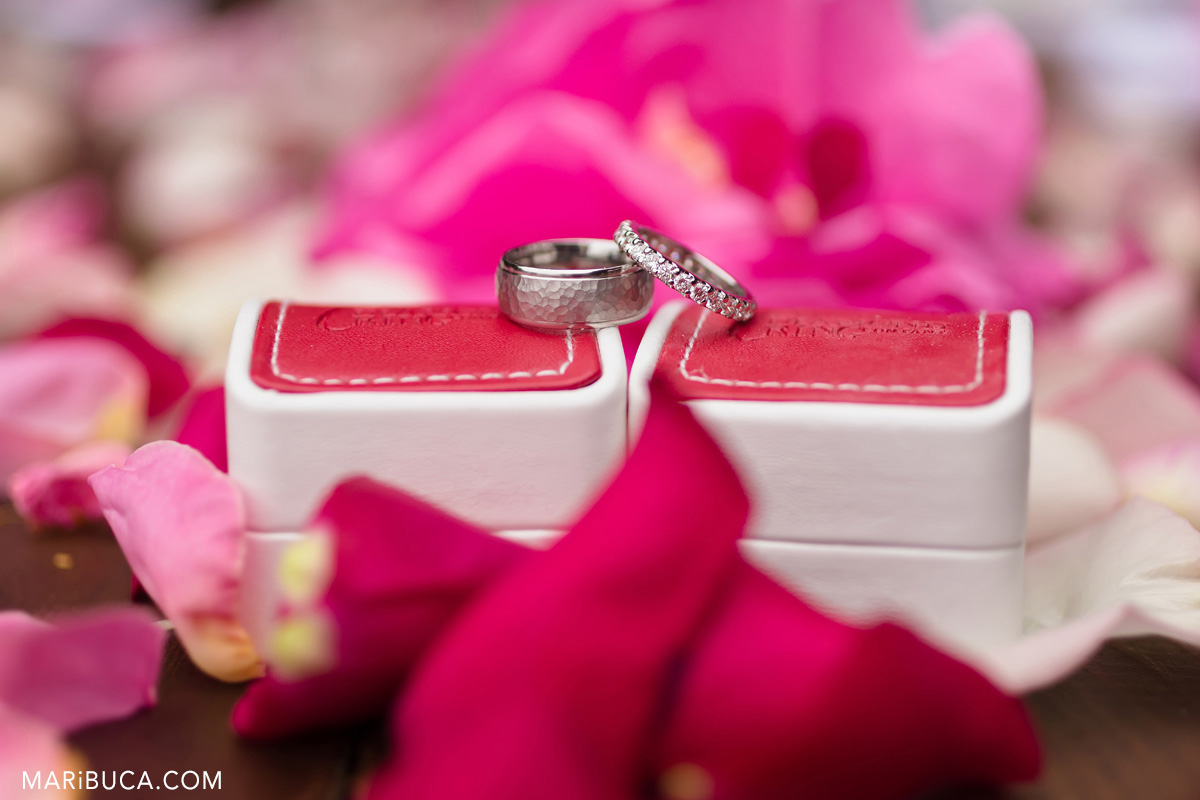 bride and groom wedding rings lay down on the red boxes and rose petals in the backgroundю