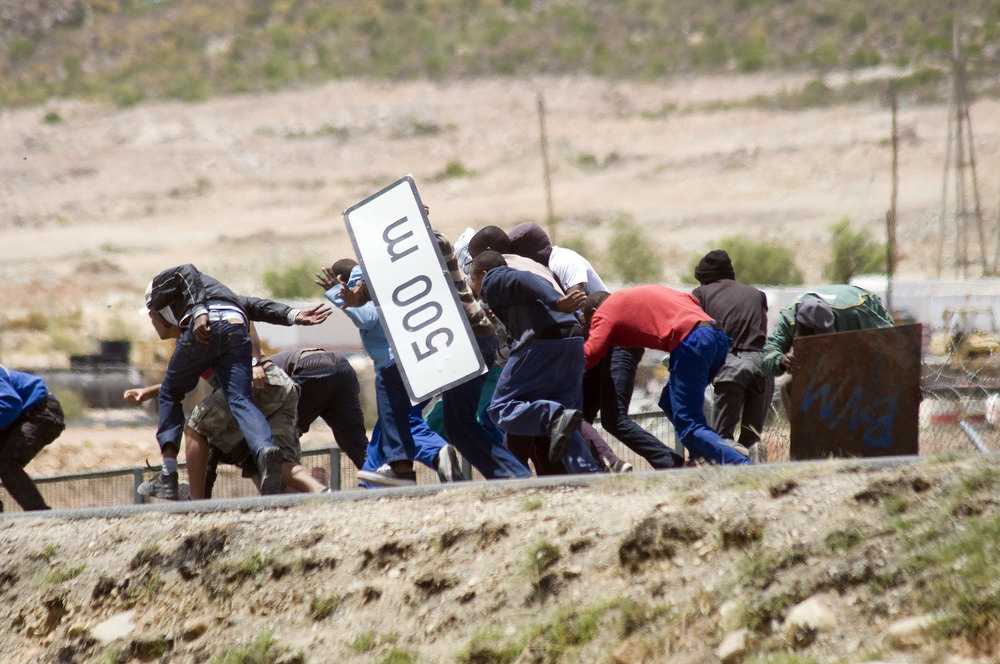 Description of . Striking farmworkers try to hide from police behind broken road signs during violent clashes, on January 10, 2012 in de Doorns, a small farming town about 140Km North of Cape Town, South Africa. The farm workers have said that they they will not return to work on the fruit growing region's farms until they receive a daily wage of at least R150($17) per day, which is about double what they currently earn. AFP PHOTO / RODGER  BOSCH/AFP/Getty Images