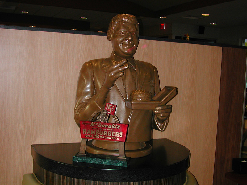 """""""The Big Mac Daddy"""". Bust of the inventor of the Big Mac -Jim Deligatti and his favorite sandwich. At the time Jim invented the Big Mac, Macdonald's had only a single smaller hamburger that sold for just 15 cents. (Later, the Big Mac sold for 45 cents at the time of inception.)  Jim changed all that in 1967 by introducing the Big Mac."""