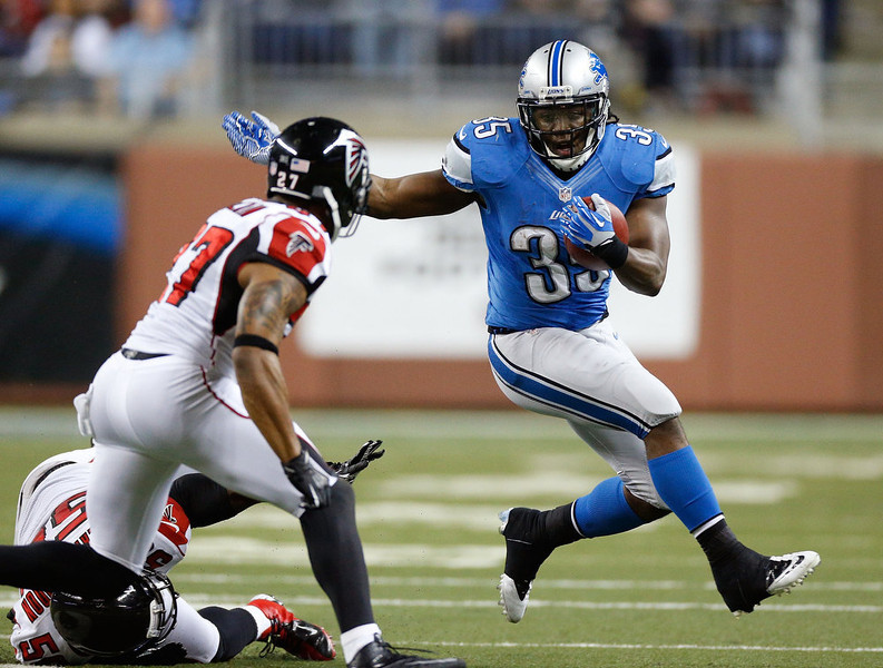 . Joique Bell #35 of the Detroit Lions tries to get around the tackle of Robert McClain #27 of the Atlanta Falcons after a second quarter catch at Ford Field on December 22, 2012 in Detroit, Michigan. (Photo by Gregory Shamus/Getty Images)