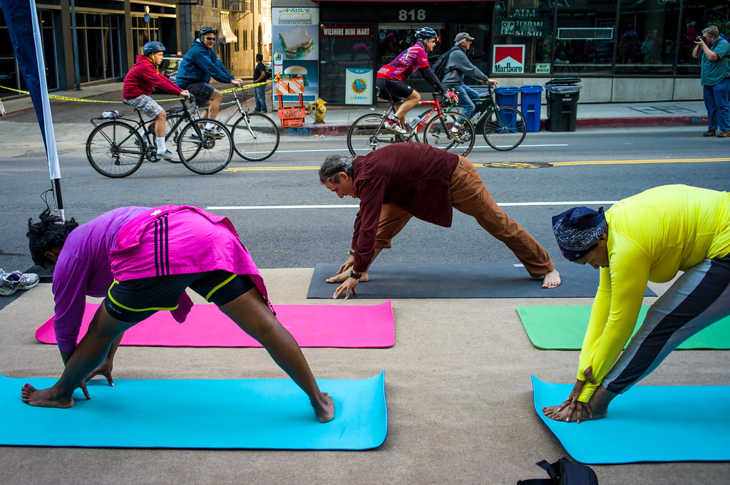 . Riders warm up with yoga along Wilshire blvd. at the start of Ciclavia Sunday April 6, 2014.  Wilshire blvd was closed between Grand Avenue and Fairfax Avenue from 9 a.m. to 4 p.m for busses only.  ( Photo by David Crane/Los Angeles Daily News )