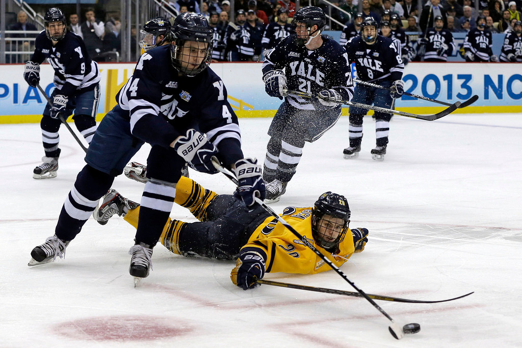 . Yale\'s Rob O\'Gara (4) clears the puck after colliding with Quinnipiac\'s Matthew Peca (20) during the first period of the NCAA Frozen Four men\'s college hockey national championship game in Pittsburgh Saturday, April 13, 2013. (AP Photo/Gene Puskar)