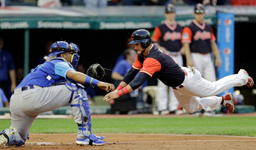 . Cleveland Indians\' Yan Gomes dives into home as Kansas City Royals catcher Salvador Perez waits for the ball during the third inning of a baseball game, Friday, Aug. 25, 2017, in Cleveland. (AP Photo/Tony Dejak)