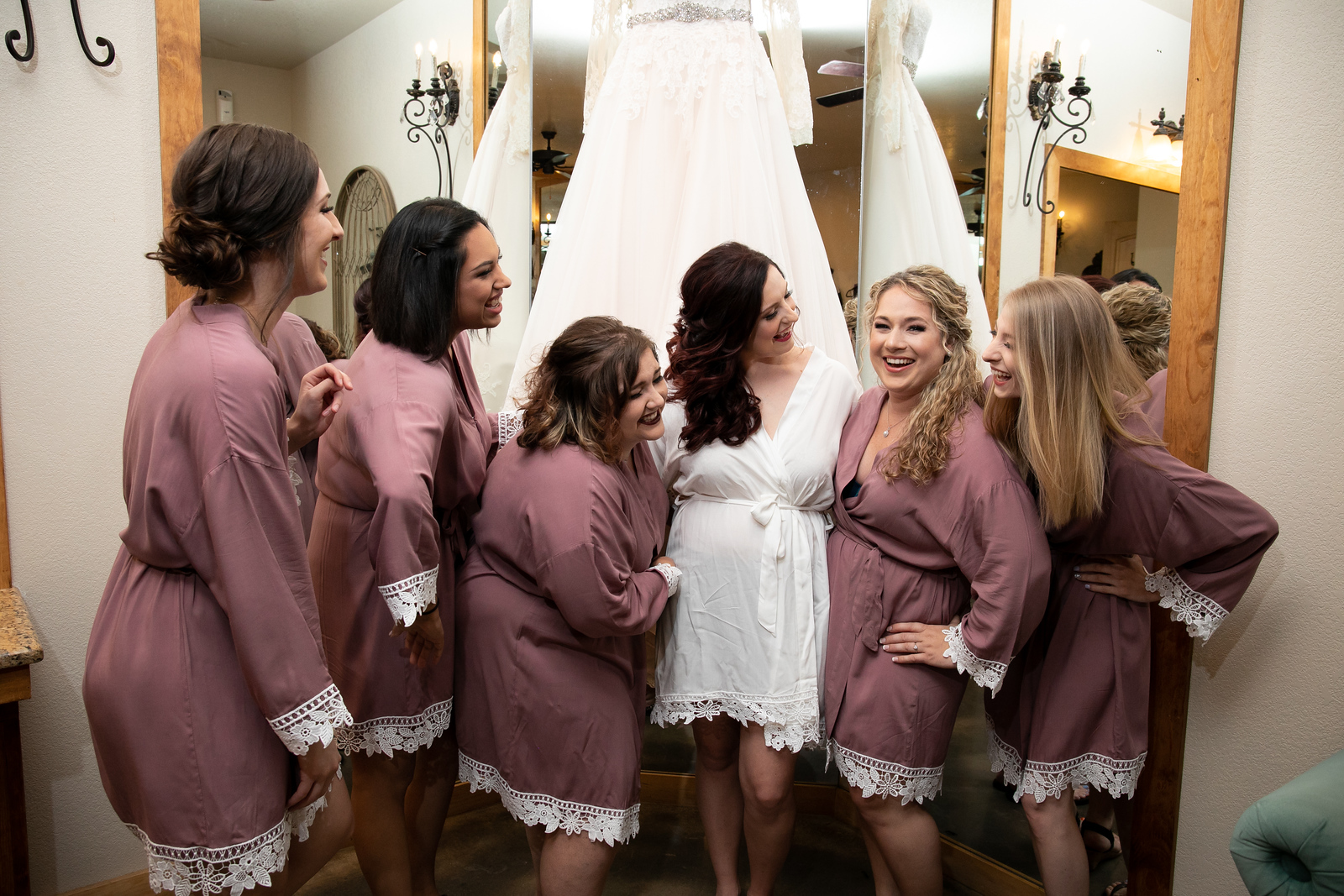five bridesmaids standing with the bride all in brown robes with lace cuffs