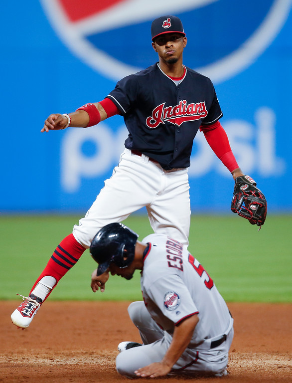. Cleveland Indians\' Francisco Lindor forces out Minnesota Twins\' Eduardo Escobar (5) at second base and throws out Max Kepler at first base to complete the double play during the fifth inning in a baseball game, Tuesday, Sept. 26, 2017, in Cleveland. (AP Photo/Ron Schwane)