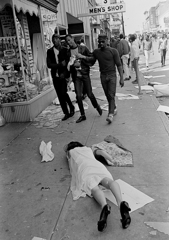 . A department store mannequin litters the sidewalk along with broken glass and placards as three African-American youths, one weeping from tear gas, leave the riot-torn sector of downtown Memphis, Tenn., March 28, 1968. Others in the background still linger on the sidewalks as looting continues around them. The rioting and looting erupted midway through a march led by Dr. Martin Luther King Jr. in support of striking garbage workers. (AP Photo/Jack Thornell)