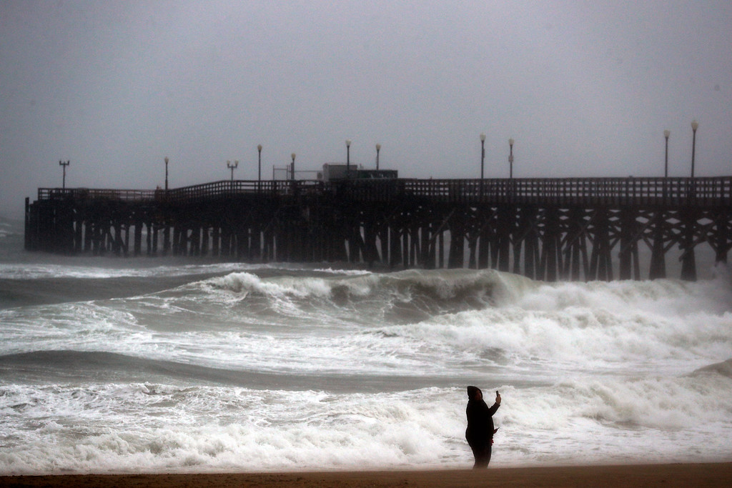 . Alex Tarin stands on the beach as waves crash against a pier Friday, Feb. 17, 2017, in Seal Beach, Calif. A major Pacific storm has unleashed downpours and fierce gusts on Southern California, triggering flash flood warnings and other problems. (AP Photo/Jae C. Hong)