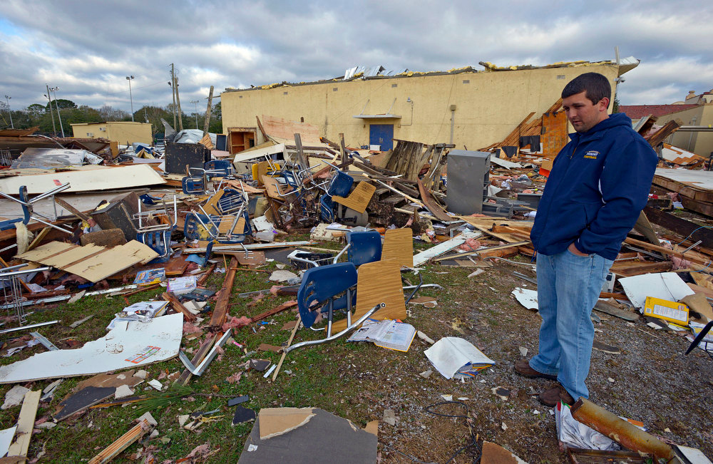 Description of . Murphy High School teacher Ryan Little looks around at the student desks and other items scattered from temporary classrooms demolished by a Christmas Day tornado at Murphy High School, as residents clean up and assess the damage  Wednesday, Dec. 26, 2012  in Mobile, Ala. With only a handful of injuries and no deaths reported statewide from the storms, the head of the state's emergency response said it was difficult to fathom how the toll wasn't worse. (AP Photo/G.M. Andrews)