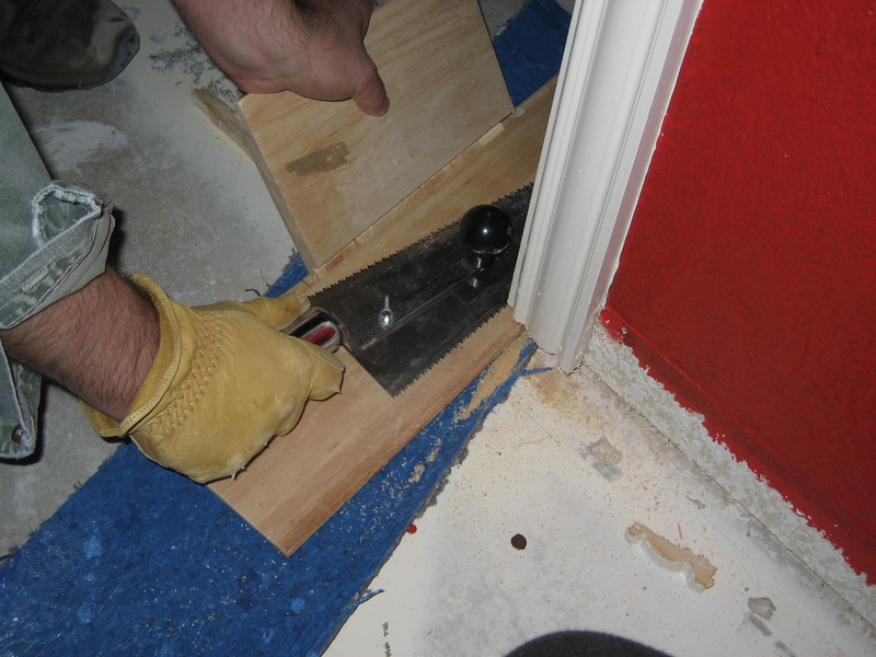Under cutting door frame and molding. Notice underlayment, and scrap piece of flooring used as support and gauge for proper height.
