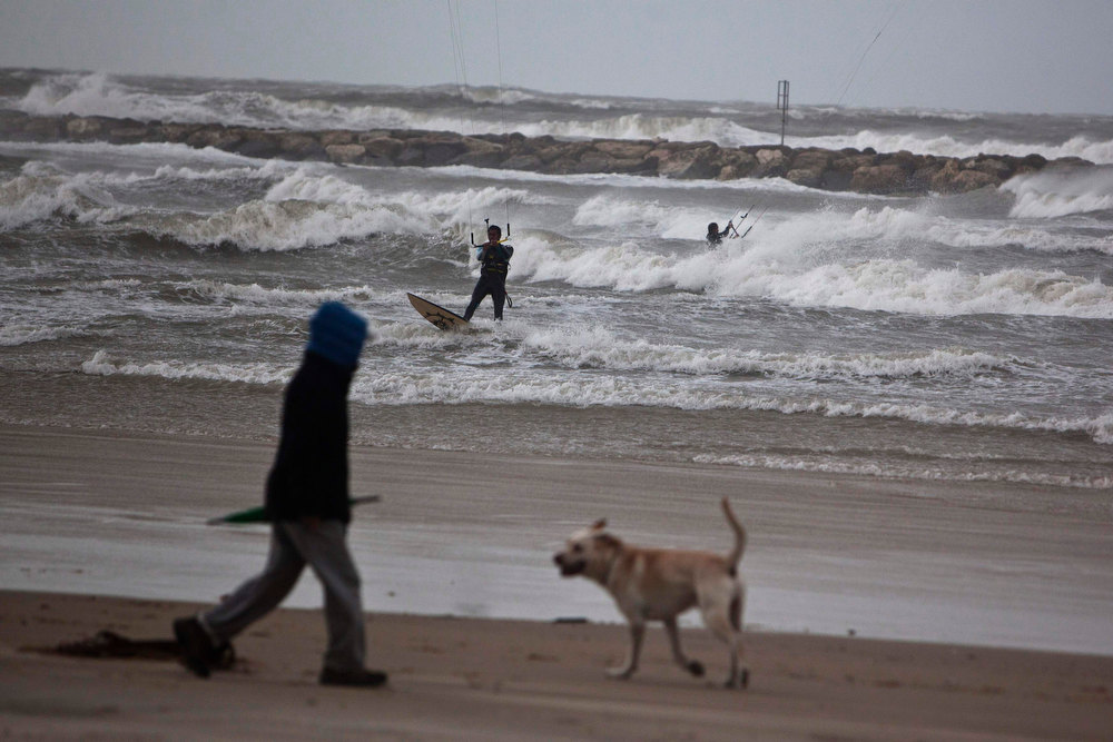 Description of . A man walks on the beach with a dog as others kitesurf in the Mediterranean Sea in Tel Aviv during stormy weather January 8, 2013. Unusually heavy winter rains forced the closure of main access routes to Tel Aviv on Tuesday, causing gridlock in and around Israel's commercial capital, authorities said. REUTERS/Nir Elias