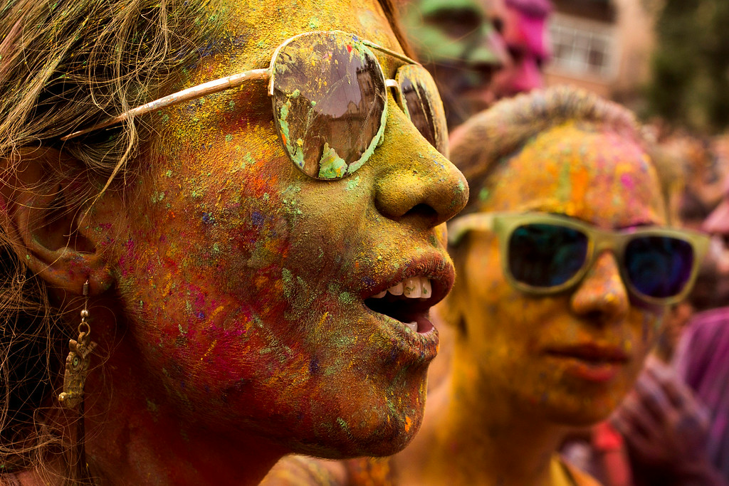 . Revelers sing as they throw special colored powders in the air during a Monsoon Holi Festival in Madrid, Spain, Saturday, Aug. 9, 2014. The festival is based on the Hindu spring festival Holi, also known as the festival of colors where participants color each other with dry powder and colored water. (AP Photo/Andres Kudacki)