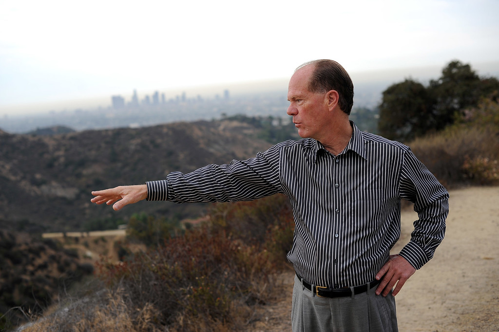 . Chris Baumgart, chairman of the Hollywood Sign Trust, points out trails that allow people to access the Hollywood sign in the hills above Hollywood, CA July 10, 2013.  The sign is celebrating its 90th anniversary this year. (Andy Holzman/Los Angeles Daily News)