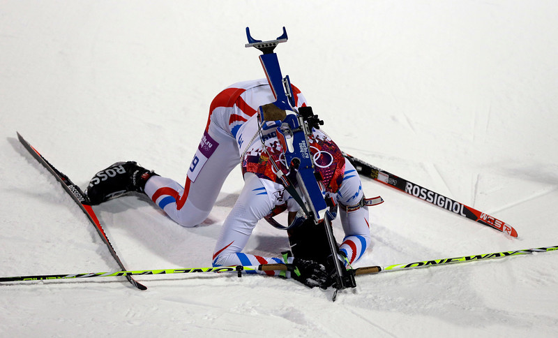 . France\'s Martin Fourcade lies on the snow after completing the men\'s biathlon 10k sprint, at the 2014 Winter Olympics, Saturday, Feb. 8, 2014, in Krasnaya Polyana, Russia. (AP Photo/Kirsty Wigglesworth)