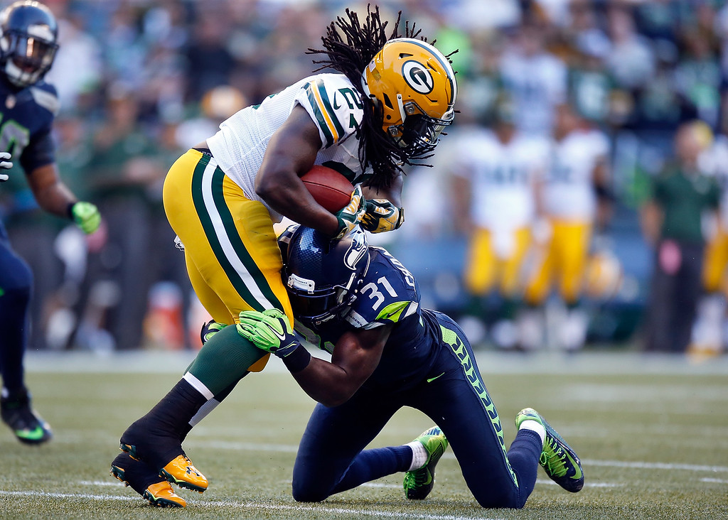 . SEATTLE, WA - SEPTEMBER 04: Running back Eddie Lacy #27 of the Green Bay Packers is tackled by safety Kam Chancellor #31 of the Seattle Seahawks during the second quarter of the game at CenturyLink Field on September 4, 2014 in Seattle, Washington.  (Photo by Otto Greule Jr/Getty Images)