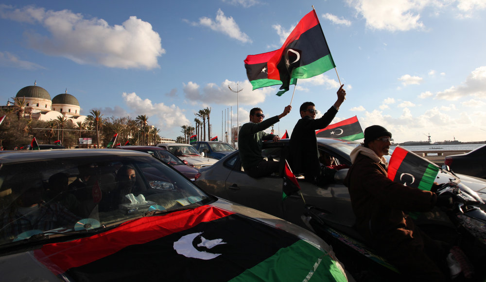 Description of . Libyans wave the national flag during commemorations to mark the second anniversary of the revolution that ousted Moammar Gadhafi in Benghazi, Libya, Friday, Feb, 15, 2013. (AP Photo/Mohammad Hannon)