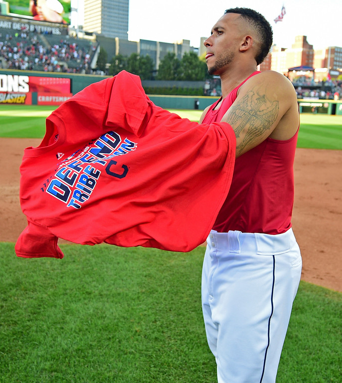 . Cleveland Indians\' Michael Brantley puts on a t-shirt after the Indians defeated the Detroit Tigers 15-0 to clinch the American League Central Division, in a baseball game, Saturday, Sept.15, 2018, in Cleveland. (AP Photo/David Dermer)