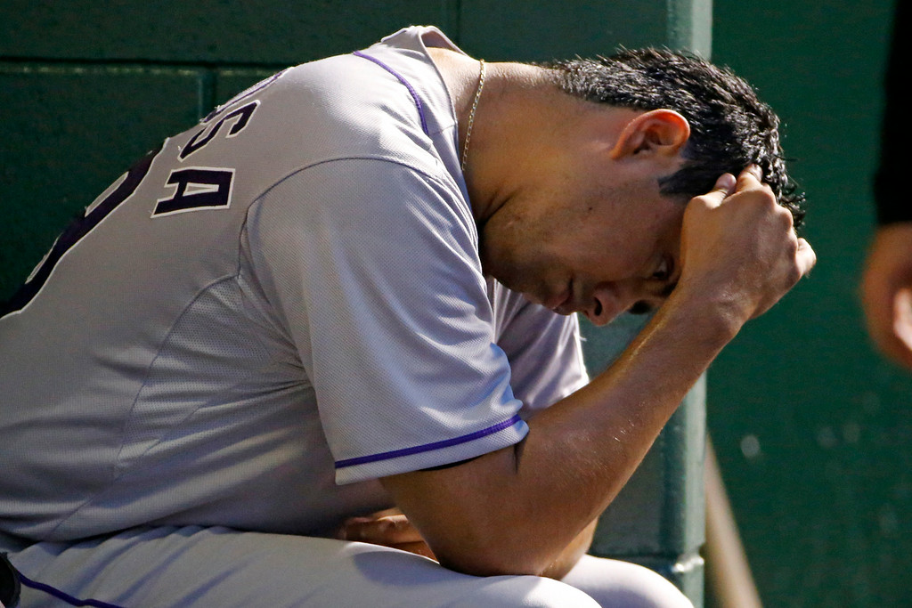. Colorado Rockies starting pitcher Jorge De La Rosa sits in the dugout during the fifth inning of a baseball game against the Pittsburgh Pirates in Pittsburgh Friday, July 18, 2014. (AP Photo/Gene J. Puskar)