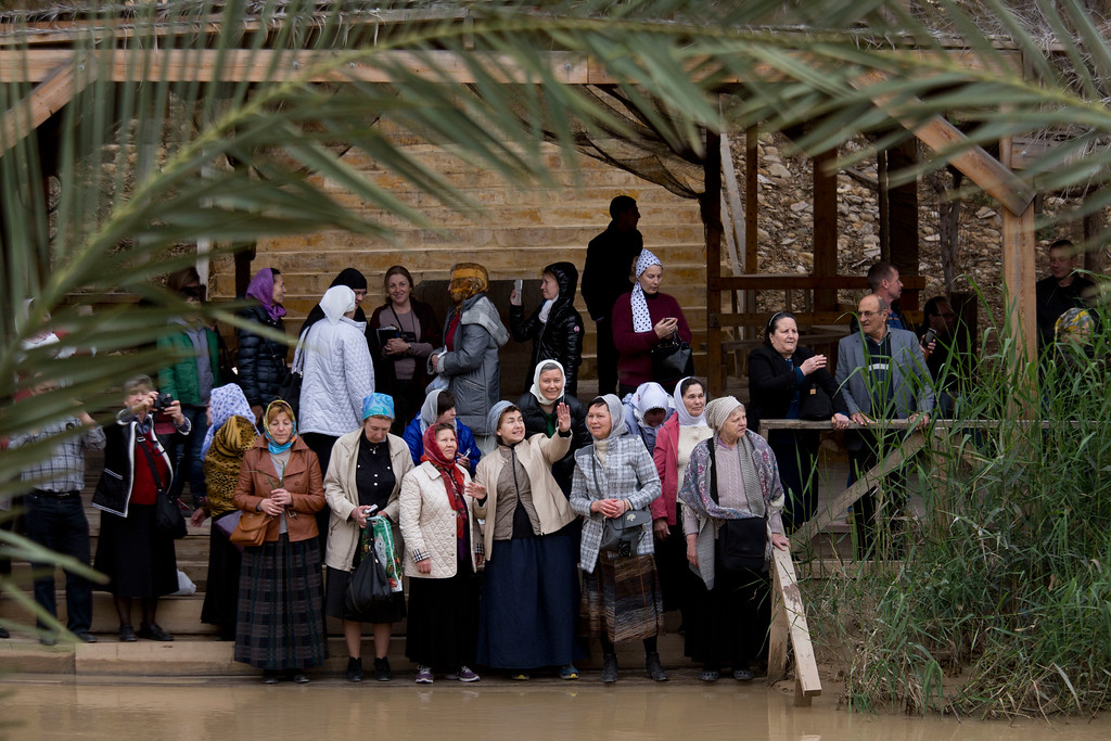 . Christians, from the Jordanian side, watch the traditional Epiphany baptism ceremony at the Qasr-el Yahud baptism site in the Jordan river near the West Bank town of Jericho, Monday, Jan. 18, 2016. The site is traditionally believed by many to be the place where Jesus was baptized. (AP Photo/Ariel Schalit)